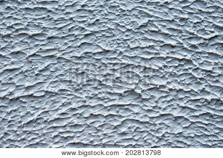 Decorative plaster coat gray-white color. Gypsum pattern on the wall in the form of a hilly surface