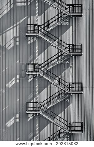 Metal staircase on industrial exterior in black and white