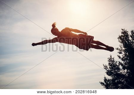 Young man levitating in the air. Sportsman jumping high in the sky. Sport and freedom concept.