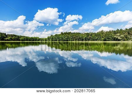 Lake landscape. Summer view of the lakeshore with white clouds reflecting in the water.