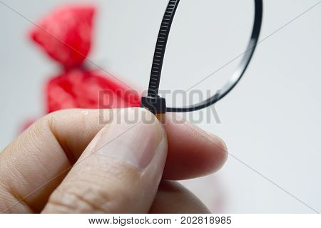 A Hand Holding The  Black Cable Tie With The Orange Bag On Background