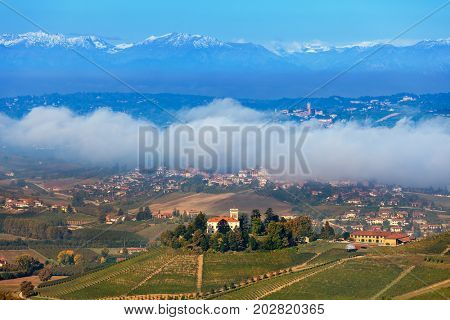 View of autumnal hills, small towns and morning fog on background in Piedmont, Northern Italy.