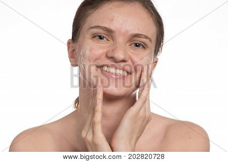 Beautiful young girl with red and white acne on her face. Before and after cream with sponge. Stop acne on a white background.