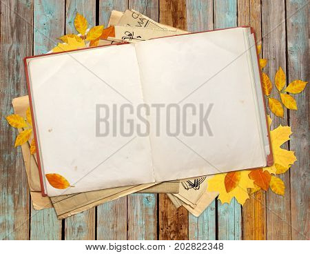 Old book and autumn leaves on old wooden boards