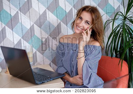A female freelancer is talking on a phone while sitting in a cafe with a portable computer on a table. Young attractive business woman is making a business call during the lunch break