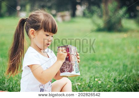 little girl seated on grass with red musical box