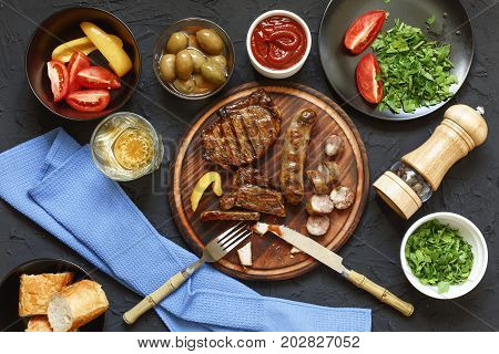 Appetizing barbecue steak at the dinner table in a restaurant with fresh vegetables, olives and wine. Italian Tradition dinner