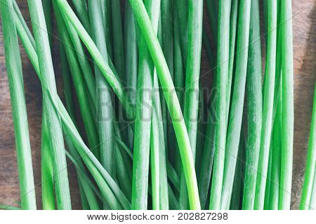 Fresh spring onion on rustic wood table. Close up on leaf of scallions or spring onion in top view flat lay. Prepare spring onion for cooking. Food and vegetable concept for background or wallpaper. Scallions in abstract background concept.