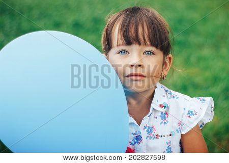 little girl holding a blue balloon and looking at camera