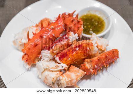alaskan king crab and seafood on white dish with seafood sauce