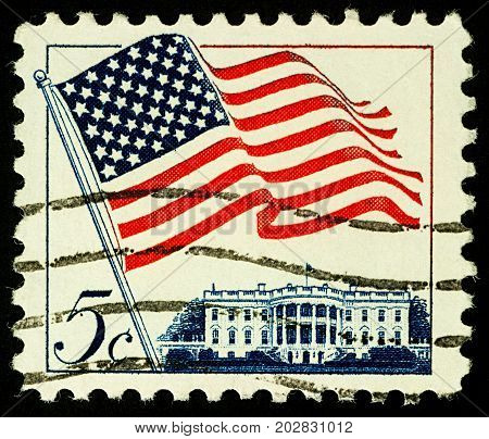 Moscow Russia - September 05 2017: A stamp printed in USA shows flag of the United States over White House in Washington DC circa 1963