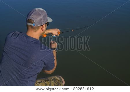 Area Trout Fishing. Fisherman With Spinning Rod In Action Playing Fish. View From Back