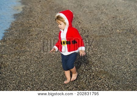 Cute baby boy in red santa coat with hood and shorts walks barefoot on grey pebble beach by sea on sunny summer day on natural background
