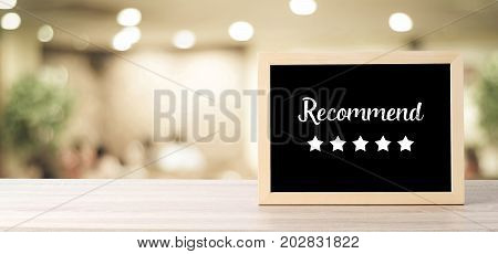 Recommend and five star on blackboard standing over blur restaurant background copy space for text food and drinks background banner