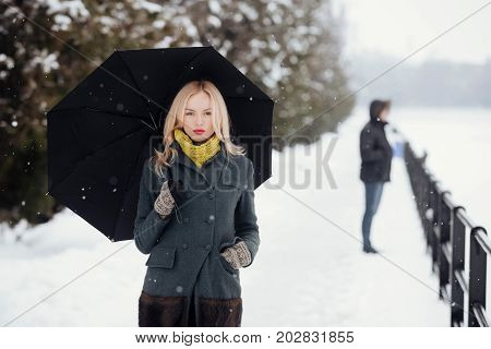 Woman with long blond hair on white snow landscape. Model in grey coat scarf and mittens. Holidays celebration concept. Christmas and new year. Girl walking with umbrella on winter day.