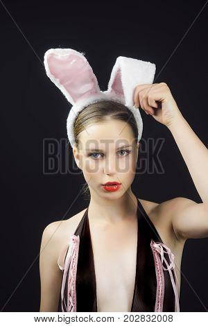 Playboy girl posing on black background. Woman with red lips wearing rabbit ears. bunny model. Easter holiday concept.
