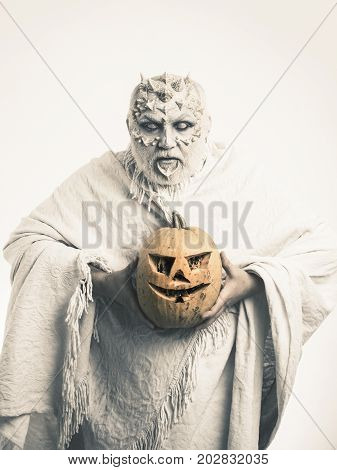 Demon with silver beard and hair. Halloween and horror concept. Monster with thorns on face. Man with orange pumpkin. Wizard with blind eyes on white background.