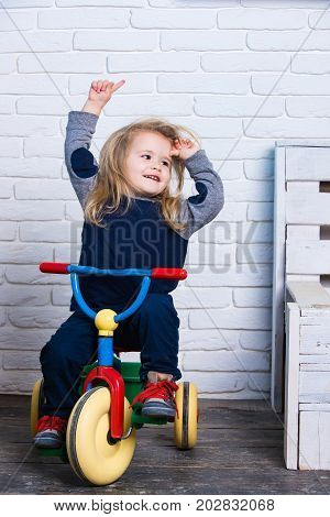 Playing and having fun. Boy riding bicycle in room. Baby cyclist with long blond hair on white brick wall. Child smiling on tricycle. Happy childhood concept.