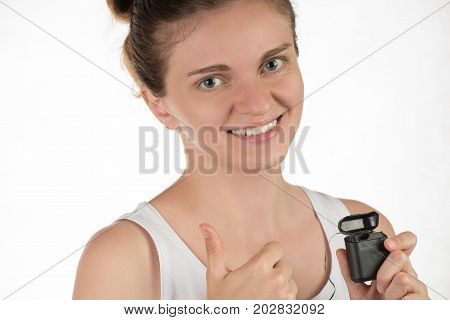 Hygiene of the oral cavity. Young girl cleans teeth with floss smiling and showing okay sign on white background.
