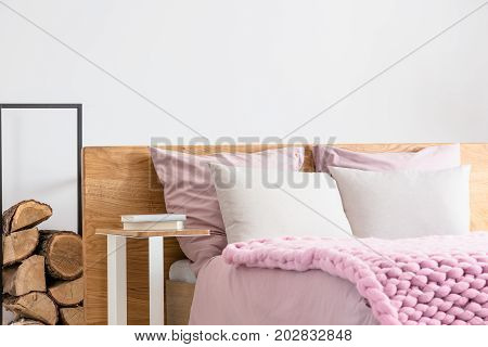 Books on bedside table next to king-size bed with pink overlay