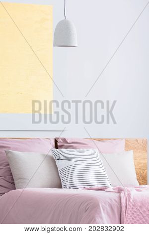 Five pillows is laying on king-size bed with pink coverlet and gold painting above
