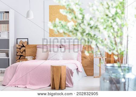Glass vase with flowers in classic bedroom with king-size bed