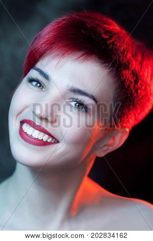 Beautiful young redhead woman smiling. Red light.