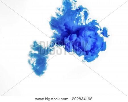 Ink swirl in water isolated on white background. The paint in the water. Soft dissemination a droplets of blue ink in water close-up. Abstract background. Soft focus.