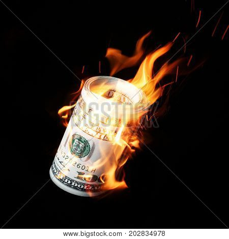 Burning one hundred dollar bills rolled black background