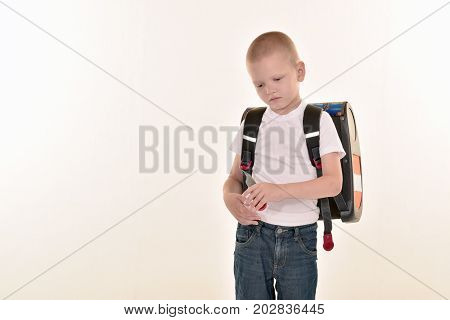 A caucasian elementary age boy posing in uniform and baccpack isolated on white background. School and education concept.