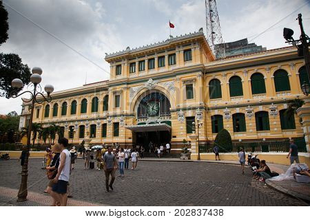 HO CHI MINH CITY (SAIGON), VIETNAM - JULY 2017 : People come to visit the central post office in neoclassical architectural style, designed and constructed by the famous architect Gustave Eiffel.