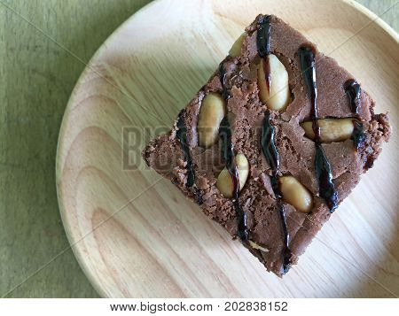 Chocolate brownie on wood plate on a table