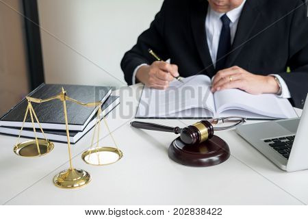 Lawyer Hand Writes The Document In Court (justice, Law) With Sounding Block And Golden Weight