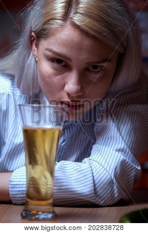 Closeup portrait of young drunken female sitting at the table with beer glass. Alcohol addiction.