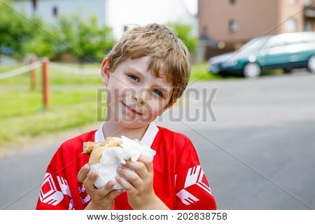 Little blond kid boy eating hot dog after playing soccer. Happy tired child in football uniform. Sports and leisure activity for children and schoolkids