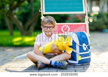 Happy little kid boy with glasses sitting by desk and backpack or satchel. Schoolkid with traditional German school bag called Schultuete on his first day to school. Child outdoors on warm sunny day