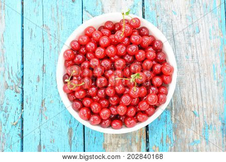 Ripe Cherries. Cherry on blue wooden background. Fresh Cherries in color bowl. Red cherry as healthy food concept.