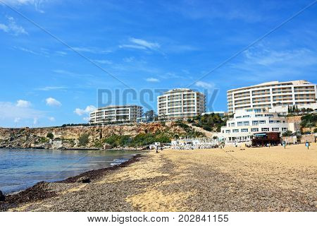 GOLDEN BAY, MALTA - MARCH 29, 2017 - View along the beach towards the Hotels on the cliff tops Golden Bay Malta Europe, March 29, 2017.