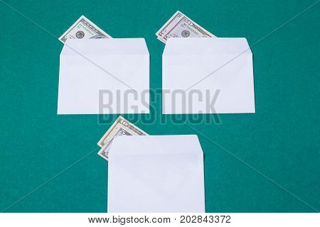 three white envelopes with money on green background