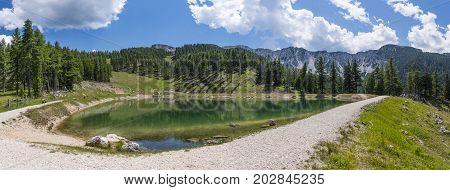 Lake on mountain Petzen with forrest and mountain Hochpetzen in the background in Carinthia Austria