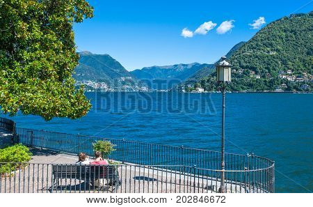 Como Italy - August 30 2010: A ypung couple sitting in the lakefront
