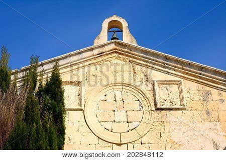 Small bell tower on top of an old church with a bricked in round window in the city centre Mdina Malta Europe.