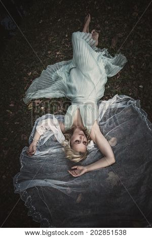 barefoot bride lie on grass and leaves with veil around her shot from above full body shot