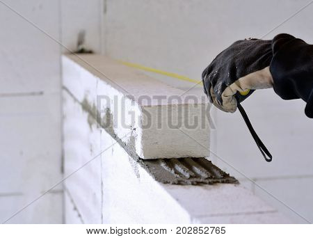 Bricklayer Using A Tape Measure