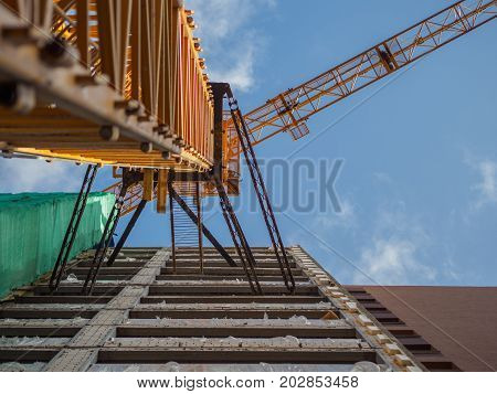 Yellow crane attached to building under construction