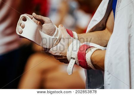 chalk in hands grips of male gymnast athlete