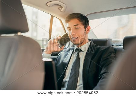 Businessman working while sitting in a car. Man beeing driven to work in his limo. Suit and tie businessman in the back seat making a call while the limo driver is driving.