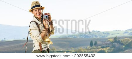 Smiling Woman Hiker Hiking In Tuscany With Retro Photo Camera