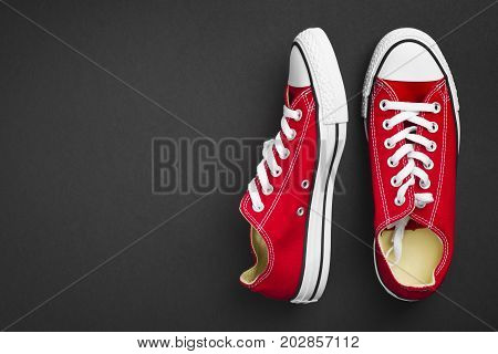 Pair of red classical gymshoes isolated on dark background