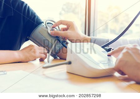 Asian Doctor Female Measuring Blood Pressure Of Male Patient At Clinic Office Room.
